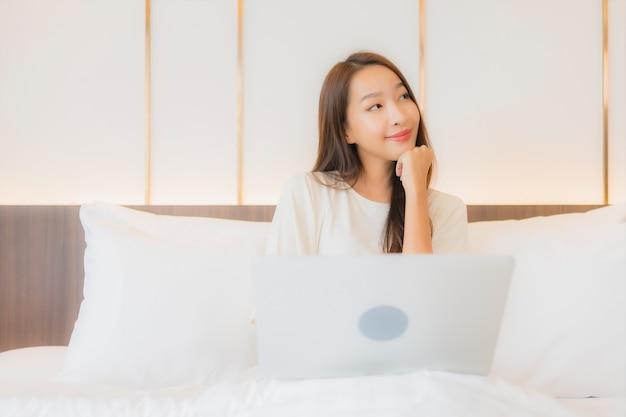 肖像画美しい若いアジアの女性は寝室のインテリアのベッドでラップトップを使用します