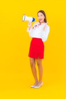 세로 아름 다운 젊은 아시아 여자 노란색에 확성기를 사용