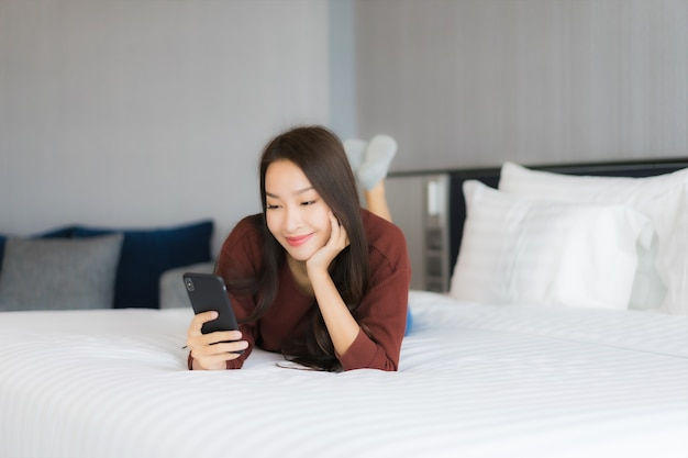 Portrait beautiful young asian woman use smart mobile phone on bed in bedroom interior