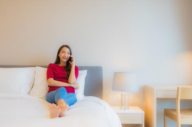 La bella giovane donna asiatica del ritratto utilizza il telefono cellulare astuto sul letto