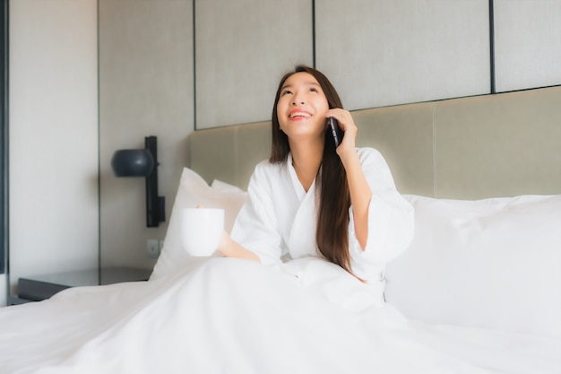 Portrait beautiful young asian woman use smart mobile phone in bedroom