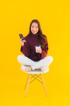 La bella giovane donna asiatica del ritratto utilizza il telefono cellulare astuto sulla sedia con fondo isolato giallo