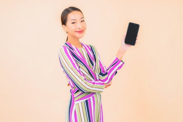 Portrait beautiful young asian woman use smart mobile phone on color