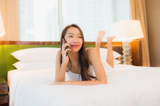 Мобильный телефон пользы женщины портрета красивой молодой азиатской умный на кровати в интерьере спальни
