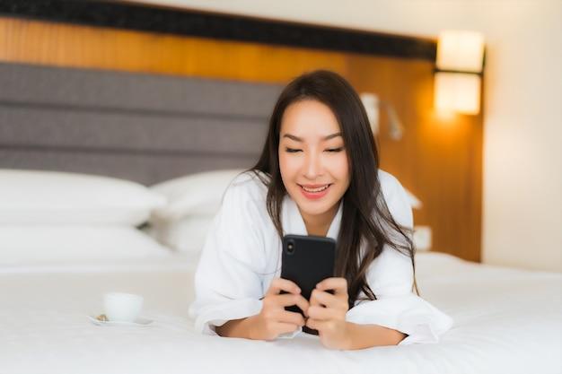 肖像画の美しい若いアジア女性は寝室のインテリアでベッドの上のスマートな携帯電話を使用します。