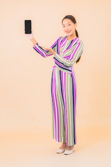 세로 아름 다운 젊은 아시아 여자 색상에 스마트 휴대 전화를 사용