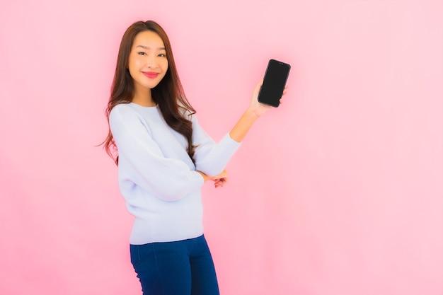 肖像画美しい若いアジアの女性はピンク色の隔離された壁にスマート携帯電話を使用します