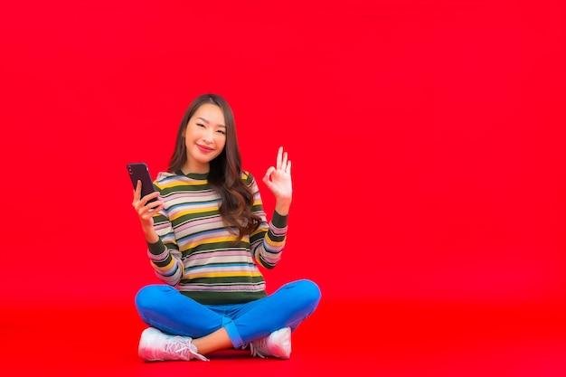 세로 아름 다운 젊은 아시아 여자 빨간색 격리 된 벽에 스마트 휴대 전화를 사용