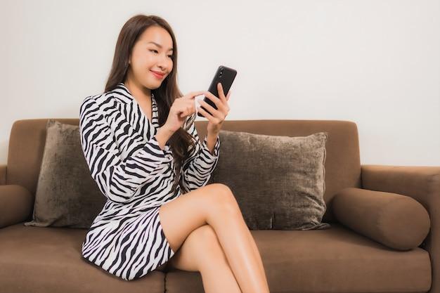Мобильный телефон пользы женщины портрета красивой молодой азиатской умный на софе в интерьере живущей комнаты