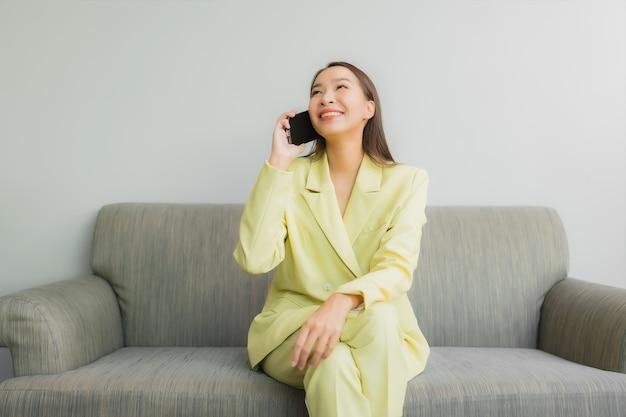 肖像画の美しい若いアジアの女性は、リビングルームのインテリアのソファーにスマートな携帯電話を使用します。