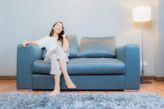 肖像画の美しい若いアジアの女性は、リビングルームのインテリアのソファでスマート携帯電話を使用します