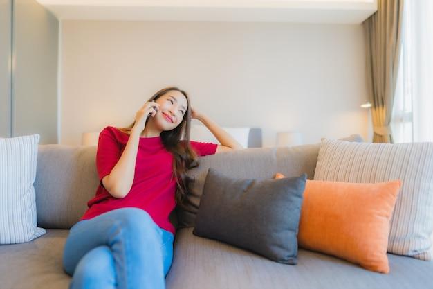 肖像画の美しい若いアジア女性はソファーでスマートな携帯電話を使用します。