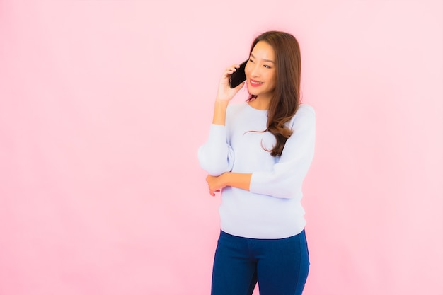 Portrait beautiful young asian woman use smart mobile phone on pink color isolated wall
