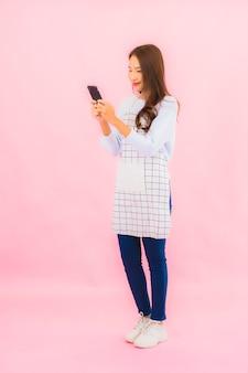 La bella giovane donna asiatica del ritratto utilizza il telefono cellulare astuto sulla parete isolata rosa