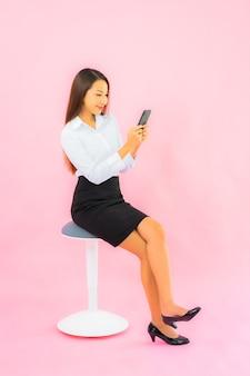 La bella giovane donna asiatica del ritratto usa il telefono cellulare astuto sulla parete isolata rosa