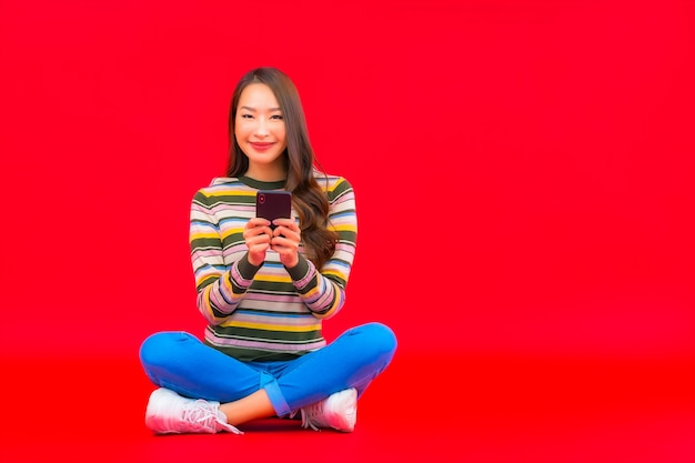 Portrait beautiful young asian woman use smart mobile phone on red isolated wall