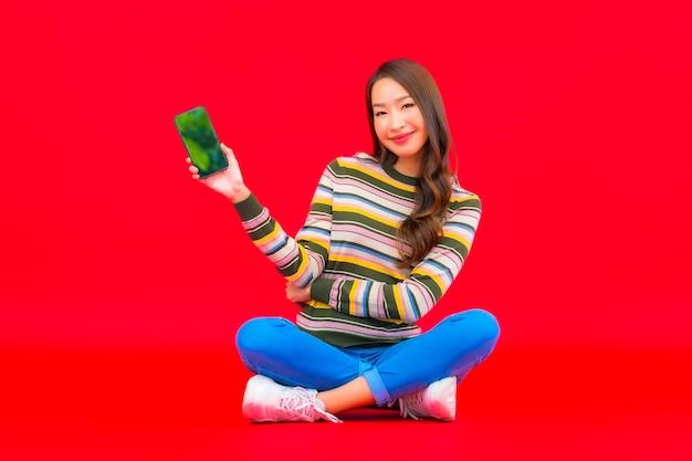 La bella giovane donna asiatica del ritratto utilizza il telefono cellulare astuto sulla parete isolata rossa