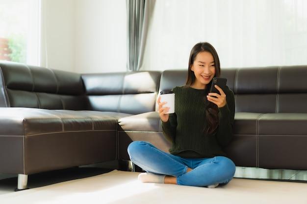 肖像画の美しい若いアジア女性はコーヒーカップとスマートな携帯電話を使用します。