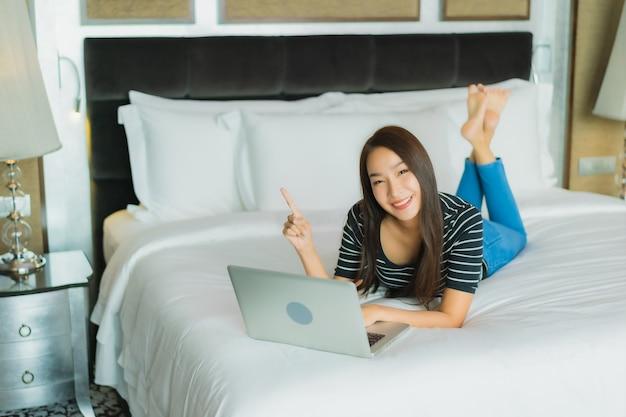 肖像画の美しい若いアジアの女性は、オンラインショッピングのコンピューターのラップトップとクレジットカードでスマートな携帯電話を使用します。