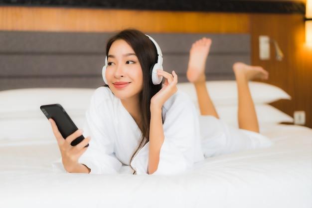 肖像画の美しい若いアジア女性は寝室のインテリアのベッドで音楽を聴くためのヘッドフォンでスマートな携帯電話を使用します。