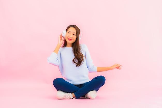 肖像画の美しい若いアジアの女性はピンクの壁で音楽を聴くためにヘッドフォン付きのスマート携帯電話を使用しています