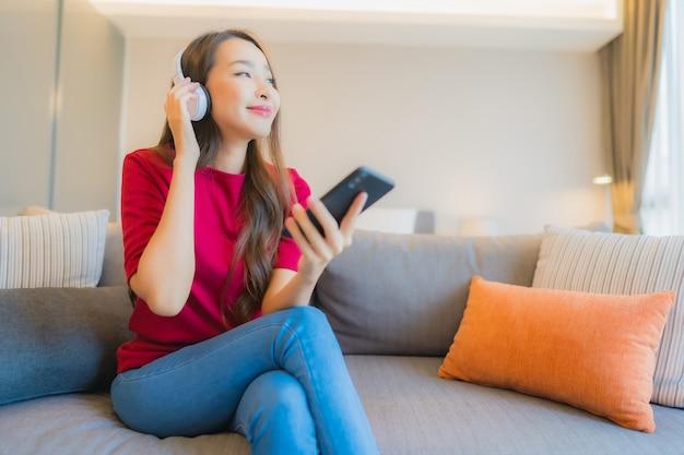 美しい若いアジア女性の肖像画は、音楽を聞くためのヘッドフォンでスマートな携帯電話を使用します。