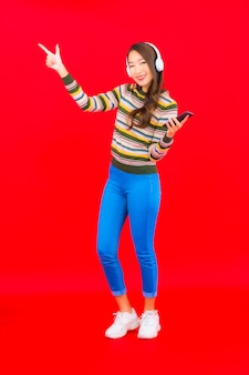 肖像画の美しい若いアジアの女性は、音楽を聴くためにヘッドフォン付きのスマート携帯電話を使用しています