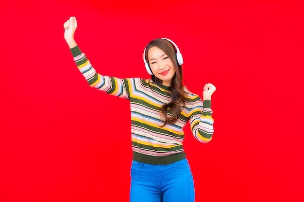 Мобильный телефон пользы женщины портрета красивой молодой азиатской умный с наушниками для слушать музыку