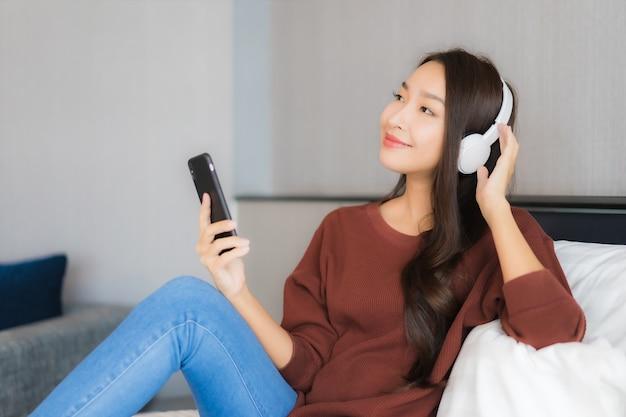 La bella giovane donna asiatica del ritratto utilizza il telefono cellulare astuto con la cuffia per ascoltare la musica sul letto nell'interno della camera da letto