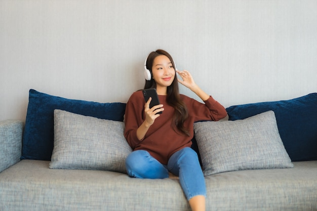 Portrait beautiful young asian woman use smart mobile phone with headphone for listen music on sofa in living room interior
