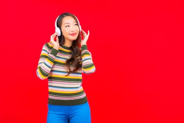 La bella giovane donna asiatica del ritratto utilizza il telefono cellulare astuto con la cuffia per ascoltare la musica