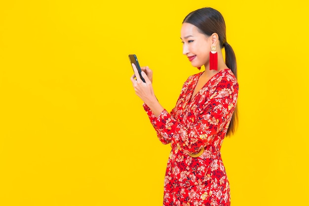 La bella giovane donna asiatica del ritratto utilizza il telefono cellulare astuto sulla parete di colore giallo