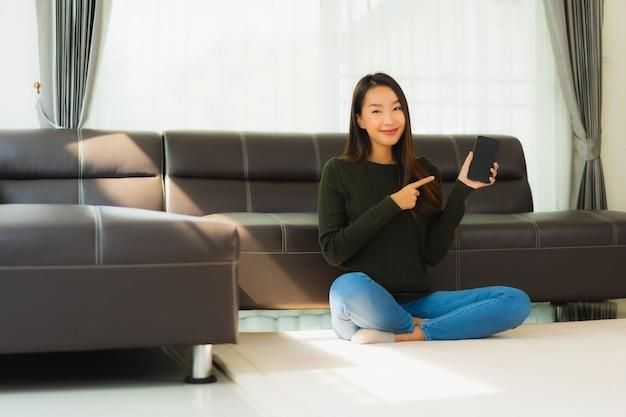 肖像画の美しい若いアジア女性はスマートな携帯電話を使用します