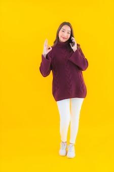 肖像画美しい若いアジアの女性はスマート携帯電話を使用します