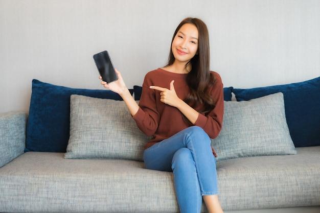 肖像画の美しい若いアジアの女性は、リビングルームのインテリアのソファーにスマートフォンを使用します。