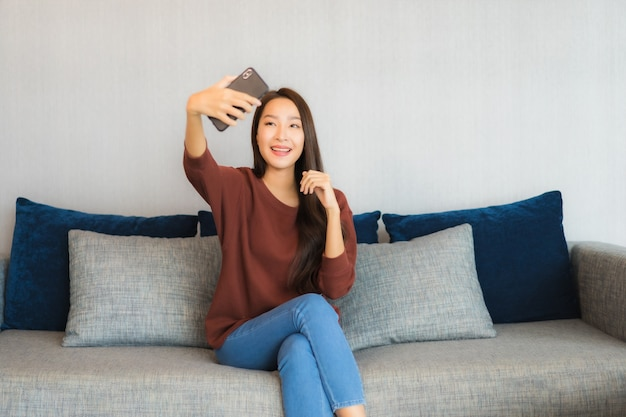 Телефон пользы женщины портрета красивой молодой азиатской умный на софе в интерьере живущей комнаты