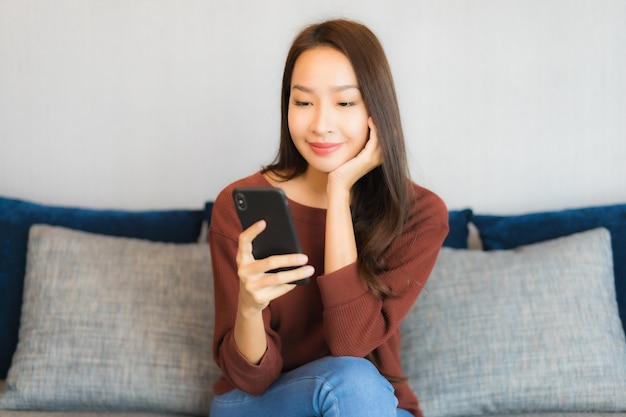Portrait beautiful young asian woman use smart phone on sofa in living room interior