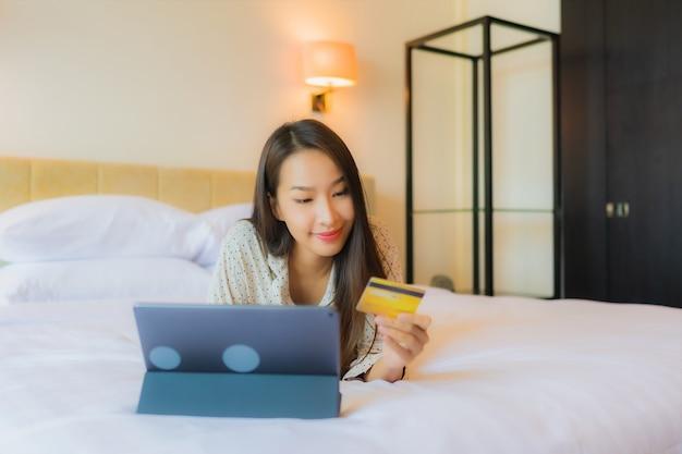 세로 아름 다운 젊은 아시아 여자는 침대에 신용 카드로 태블릿을 사용