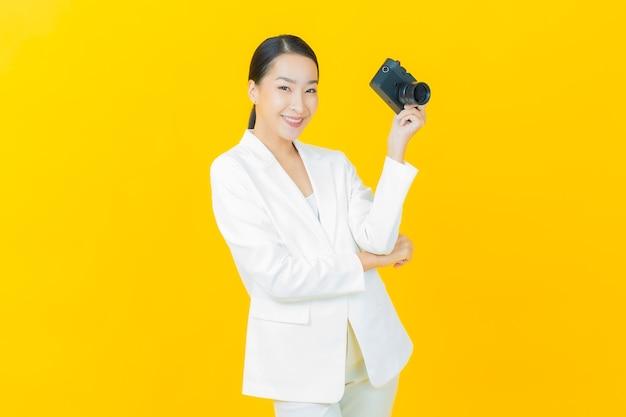 Женщина портрета красивая молодая азиатская использует камеру на стене цвета