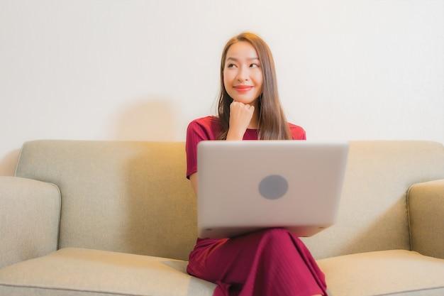 リビングルームのインテリアのソファでコンピューターのラップトップを使用して美しい若いアジアの女性の肖像画