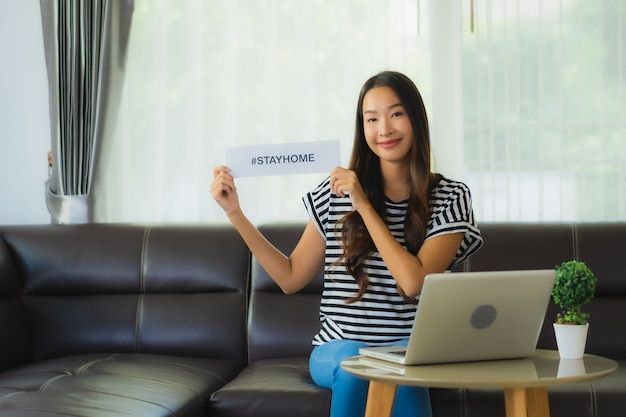 Portrait of beautiful young asian woman using laptop on sofa with stay home paper