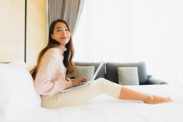 ベッドの上の携帯電話でラップトップを使用して美しい若いアジア女性の肖像画