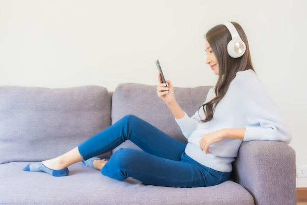 스마트 휴대폰과 헤드폰을 사용하여 거실에서 음악을 들을 수 있는 아름다운 젊은 아시아 여성의 초상화