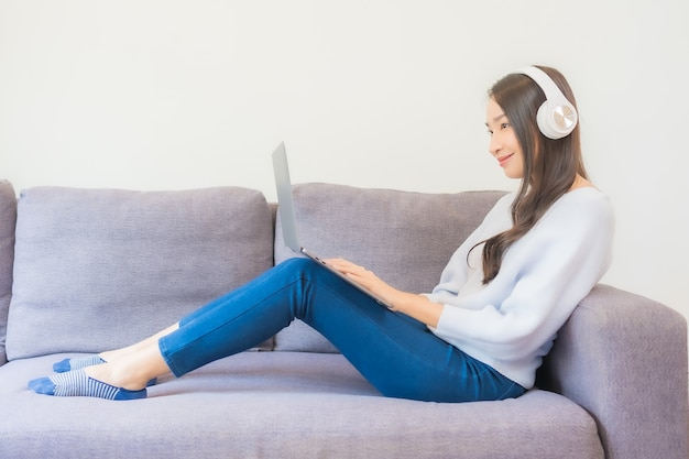 リビングルームで音楽を聴くためにスマートな携帯電話とヘッドフォンを使用して美しい若いアジアの女性の肖像画