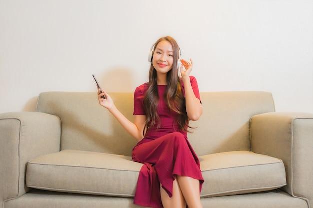 Женщина портрета красивая молодая азиатская используя умный мобильный телефон и наушники для прослушивания музыки на софе