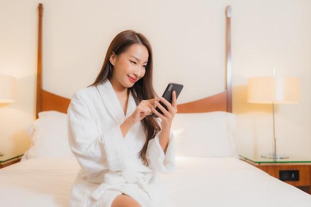 Bella giovane donna asiatica del ritratto che per mezzo del telefono cellulare astuto sul letto nell'interno della camera da letto