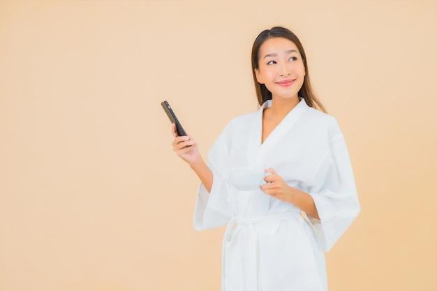 Bella giovane donna asiatica del ritratto che per mezzo del telefono cellulare astuto sul beige