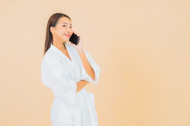 Portrait beautiful young asian woman using smart mobile phone on beige