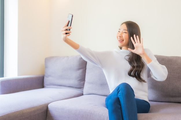 Женщина портрета красивая молодая азиатская используя умный мобильный телефон на софе в интерьере живущей комнаты
