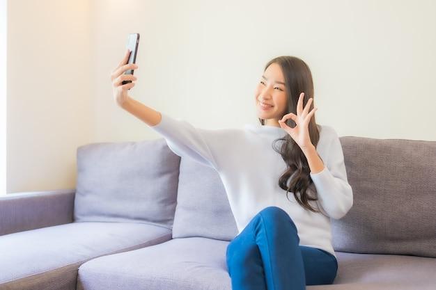 リビングルームのインテリアのソファでスマート携帯電話を使用して美しい若いアジアの女性の肖像画